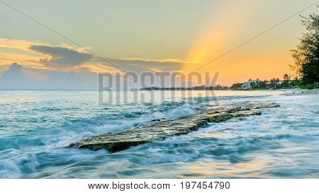 Sunset over a flat rock emerging from the Caribbean sea at Cemetery Beach, Grand Cayman