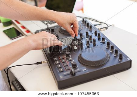 music technology, holiday party concept - male hands of Dj mixes audio track, beautiful black hi end disc jockey mixing device, digital concert equipment, resort entertainments, selective focus