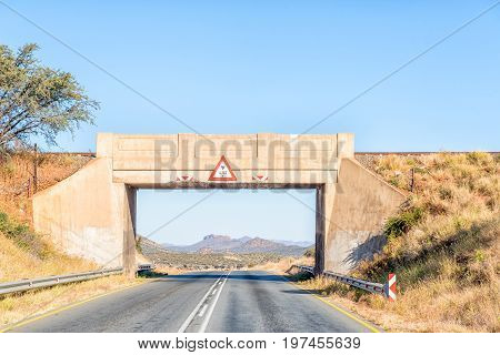 A railway bridge over the B1-road frames a mountain scene south of Windhoek the capital city of Namibia