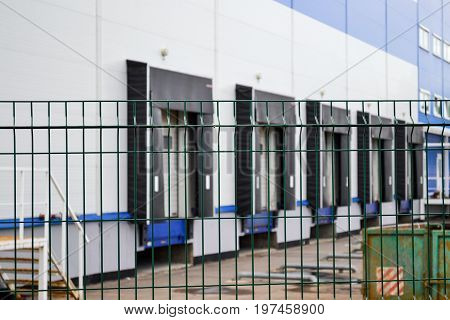 Large distribution warehouse in the background behind a latticed fence