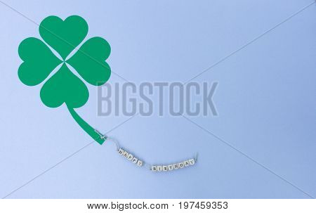 The words Happy Birthday on a cord and a cloverleaf
