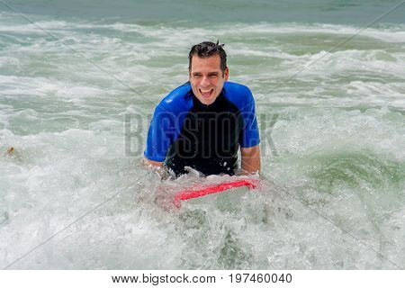 A happy man pushes down on a boogie board at the end of his body surfing run. He is in white water by the shoreline of the ocean.