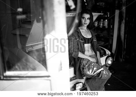 Girl worker in dirty overalls and t-shirt stands in workshop near opened capote of retro car. Black and white image.