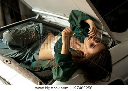 Girl worker in dirty overalls rest in workshop on opened trunk of car. Closeup.