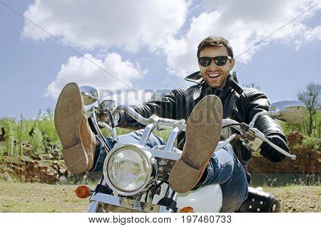 Biker man in black leather jacket sitting on motorcycle