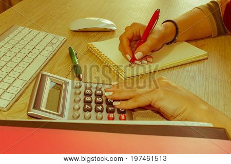 Close up view of bookkeeper or financial inspector hands making report calculating or checking balance. Business plan with money calculator and pen on the table - Retro color