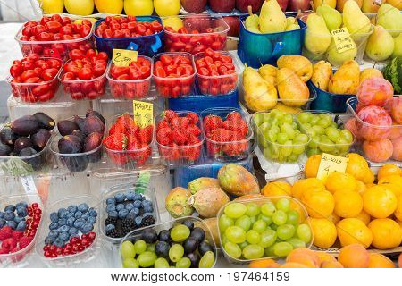 Venice, Italy - september 2016: Rialto fish markets. Fishmonger at work.Tablets with price of berries, pears, figs, tomatoes, grapes, apricots