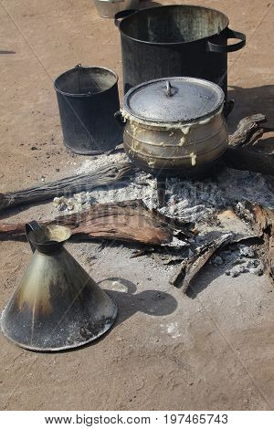 Cooking corn cereal in contrule on fire in the village Botswana.