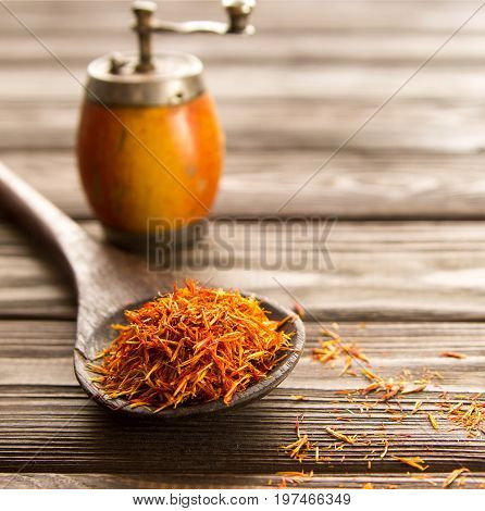 Spice saffron in a wooden spoon on a wooden backgroundbehind vintage handmill. Close-up.