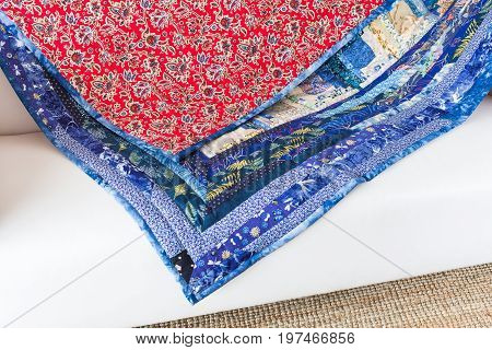 quilting, interior, culture, hobby, passion, handcraft concept - bright multicolored blanket is decorated with various flowers, leaves, dragonflies and ladybugs