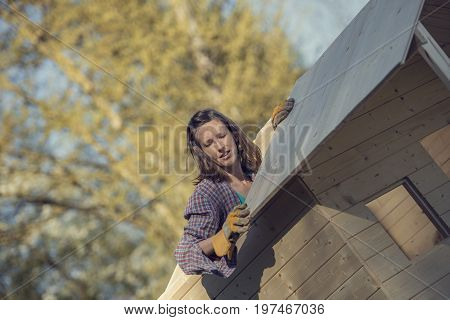 Woman in check shirt putting a wooden plank on roof of garden shed a do-it-yourself construction toned retro effect.