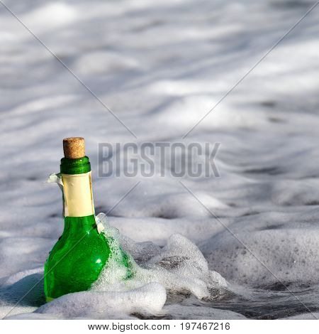 Empty bottle of wine in sunshine sea surf