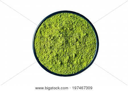 Ground matcha green tea powder in a round cast iron cup isolated on white background clipping path included view from above.
