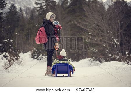 Retro vintage style image of a young mother pulling her child through winter snow on a sledge turning and smiling at him in a mountain pine forest.
