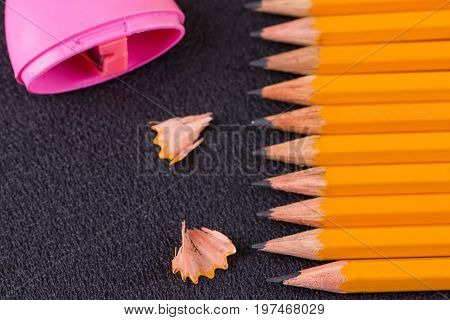 Simple pencils and a pink pencil sharpener on a black background
