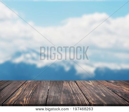 image of wooden table in front of abstract blurred background of mountain. can be used for display or montage your products. Mock up for display of product