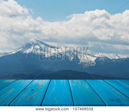 image of wooden table in front of abstract blurred background of mountain. can be used for display or montage your products. Mock up for display of product.