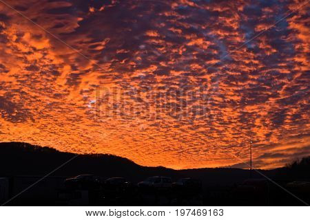 Amazing sunset with big orange fire in the sky on a road in Slovenia