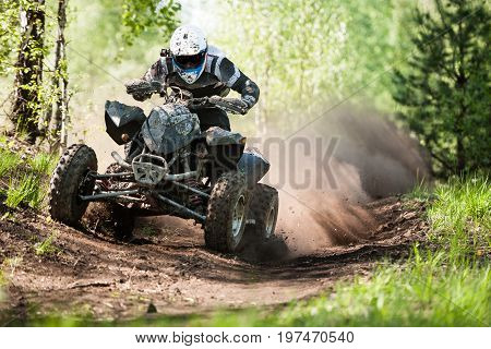ATV rider creates a large cloud of dust and debris on sunny day