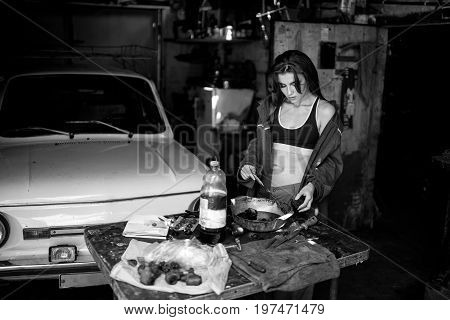 Girl worker in green overalls and t-shirt stands in workshop among tools and lubricates spare parts from car. In her hands she holds brush next to her there is bottle of grease. Black and white image.
