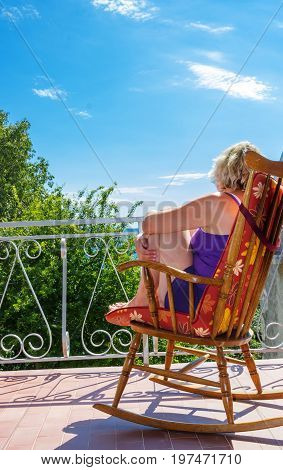 woman on a balcony feeling alive and free, looking view of beach sea on hot summer day. Travel holidays vacation