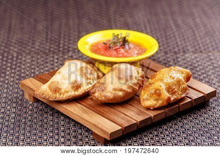 Typical Spanish empanadas with salsa souse on wooden board.