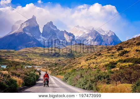 Girl standing with her bicycle on the road leading to the impressive Cuernos del Paine peaks in Torres del Paine National Park, Chile, South America
