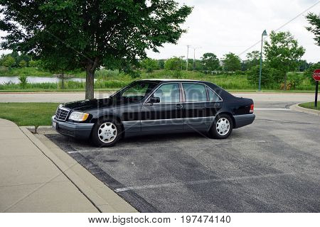 PLAINFIELD, ILLINOIS / UNITED STATES - JUNE 30, 2017: A 1996 black Mercedes-Benz S420 luxury sedan is parked in the parking lot of the Edward Plainfield Outpatient Center.
