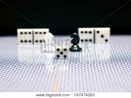 Dice chess horses and dominoes on reflective surfaces Accessories for popular board games on a dark background