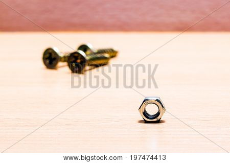 Metal shiny nut and screws with threaded tools for fastening on a wooden background