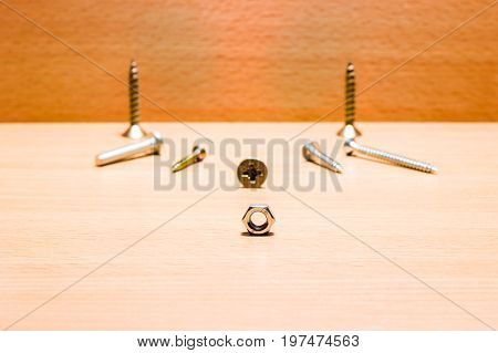 Nut on the background of metal screws for fastening small useful tools very durable and reliable