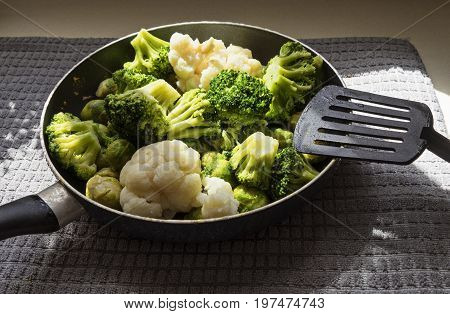 The pan with fresh defrosted vegetables: cauliflower, broccoli, brussels sprouts and kitchen spatula