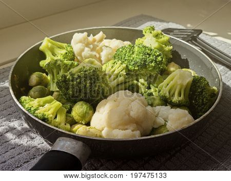 View of the pan with fresh defrosted vegetables: cauliflower, broccoli, brussels sprouts and kitchen spatula