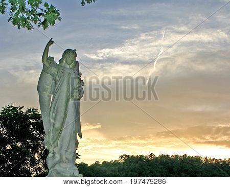 statue of an angel pointing skyward, against a colorful sunset