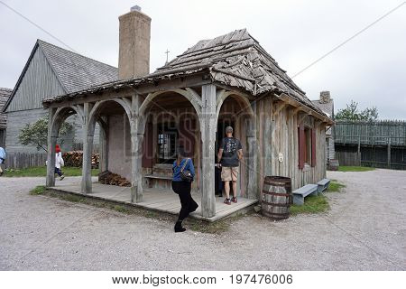 MACKINAW CITY, MICHIGAN / UNITED STATES - JUNE 18, 2017: Visitors enter the guardhouse in Fort Michilimackinac, in the Colonial Michilimackinac State Park.