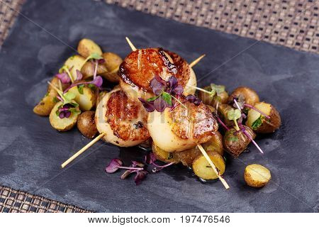 Grilled scallops with roasted young potatoes on stone