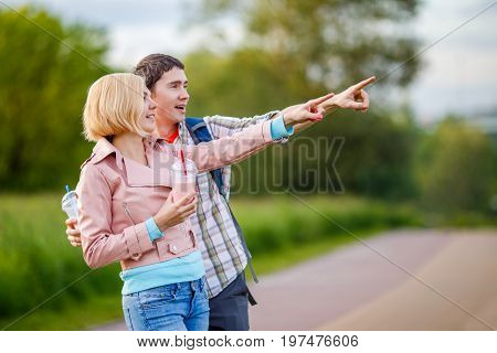 Photo of pair of girls and guy showing hand in distance at park during day with milkshake in hands