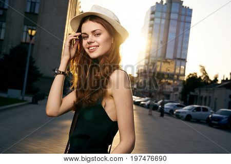 Young beautiful woman in a white hat walking outdoors in the city, megapolis.