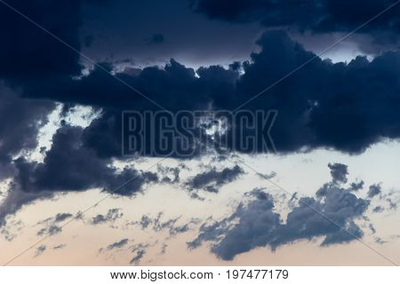 chunky smoky cumulus clouds in a contrasty sky at sundown