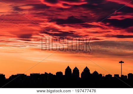 colorful fiery sky at sundown with altocumulus clouds over the city skyline