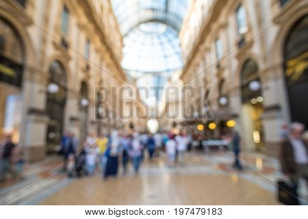 Blurred image bokeh of People walking around Galleria Vittorio Emanuele II one of the world's oldest shopping malls.