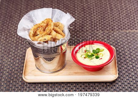 Deep Fried Calamari Rings in bucket with Sauce Bowl on wooden plate.