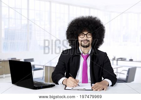 Portrait of entrepreneur smiling at camera while writing on paper with laptop on the desk shot in the office room