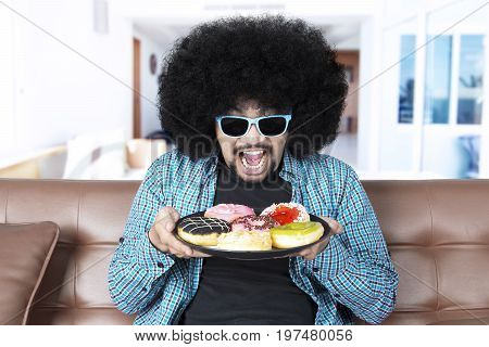 man with curly hair holding a plate of tasty donuts while wearing sun glasses and sitting on the sofa at home