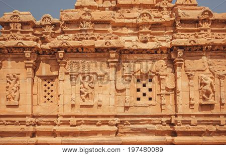 Background of an ancient walls of Hindu temples with reliefs. Architecture landmark in Pattadakal, India. UNESCO World Heritage site of 7th and 8th-century