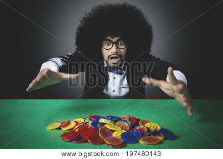 Portrait of desperate man with curly hair losing casino chip in gambling
