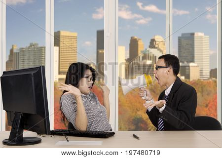 Image of male manager is screaming at his secretary through megaphone while working in the office with autumn background on the window