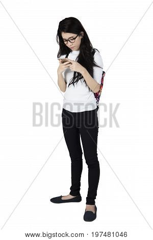 Full length of a young Asian female student standing in the studio while using cellphone isolated on white background