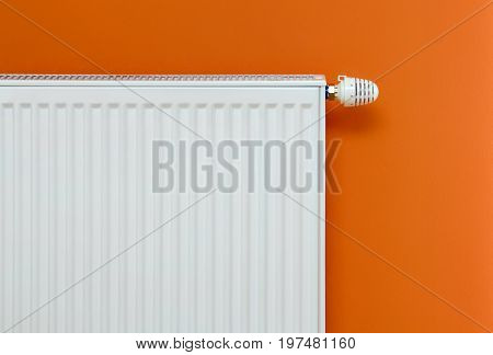 Heating Radiator Attached on the Orange Wall
