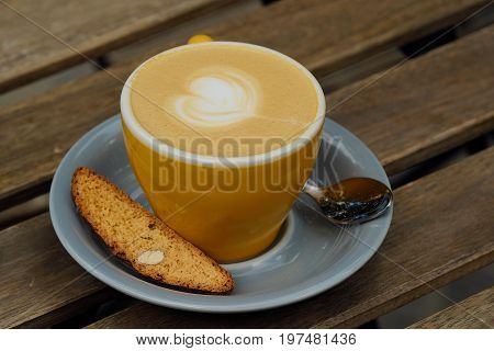 A mug of delicious cappuccino and croutons with nuts